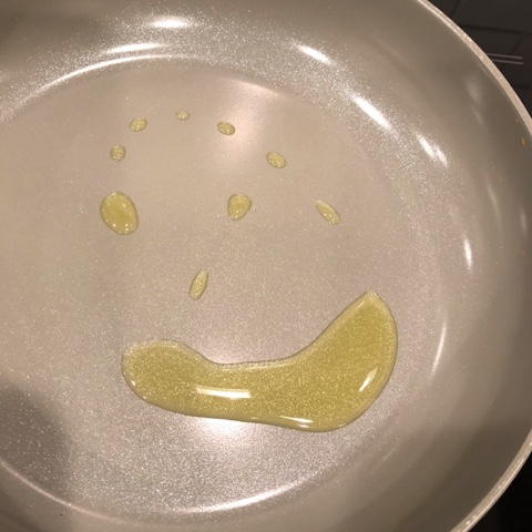 oil making a smiley face in a frying pan