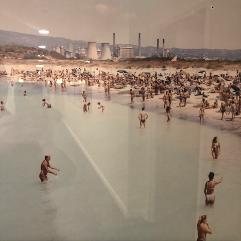 bathers on a beach with nuclear reactors in the background