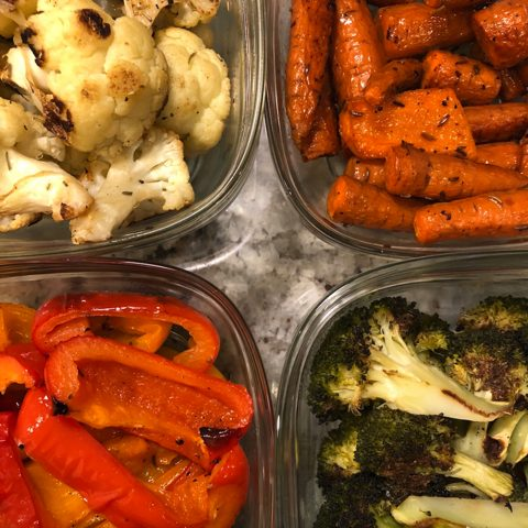 Roasted vegetables in glass containers: cauliflower, carrots, red peppers and broccoli
