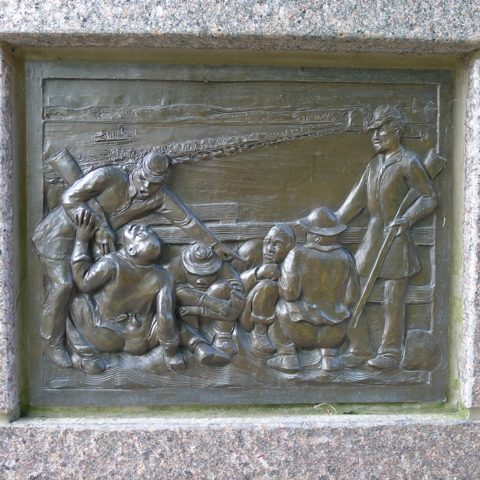 Panel from The Black Brigade memorial, showing Black men squatting in a pen while white guards oppress them