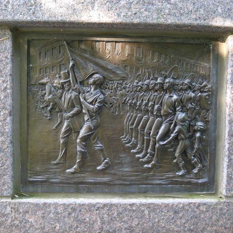 Panel from The Black Brigade memorial, showing The Black Brigade in a parade in downtown Cincinnati