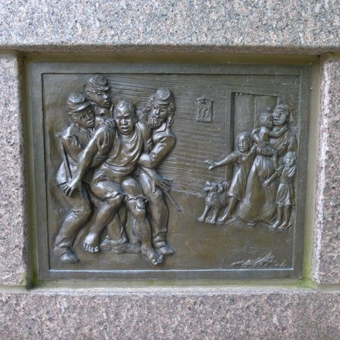 Panel from The Black Brigade memorial, showing a Black man being hauled from his home, while his wife and children look on in horror