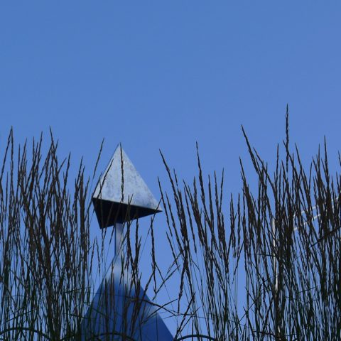 a metal sculpture above some grasses with blue sky