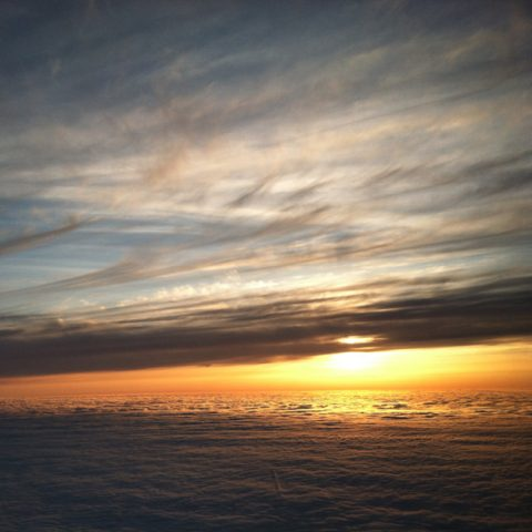 photo of sunset taken from an airplane, with a layers of clouds above and below and the sun shining through between