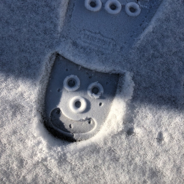 bootprint in snow, with a smiling face on the heel