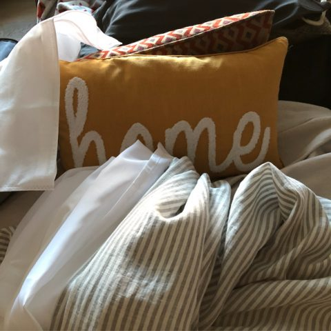 mustard colored pillow that says home in white letters, on a pile of linens