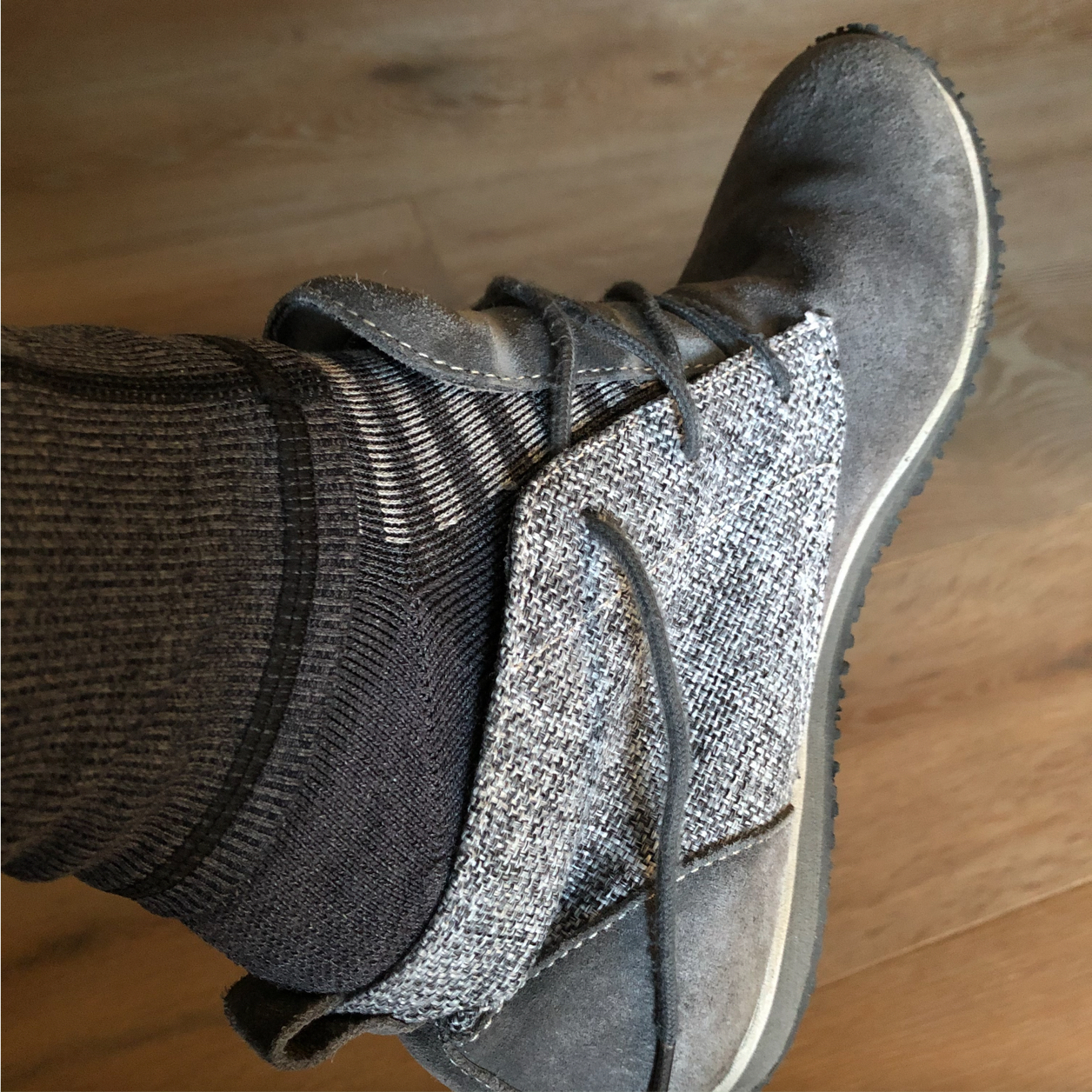 Close up of a grey suede shoe with grey and white striped socks with grey leggings