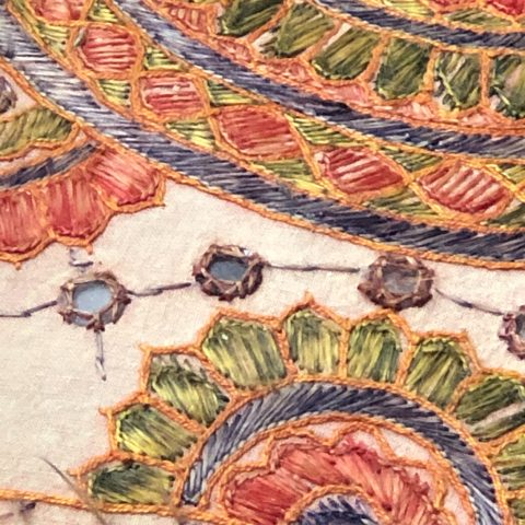 Close up of colorful embroidery shaped like wheels on a linen background