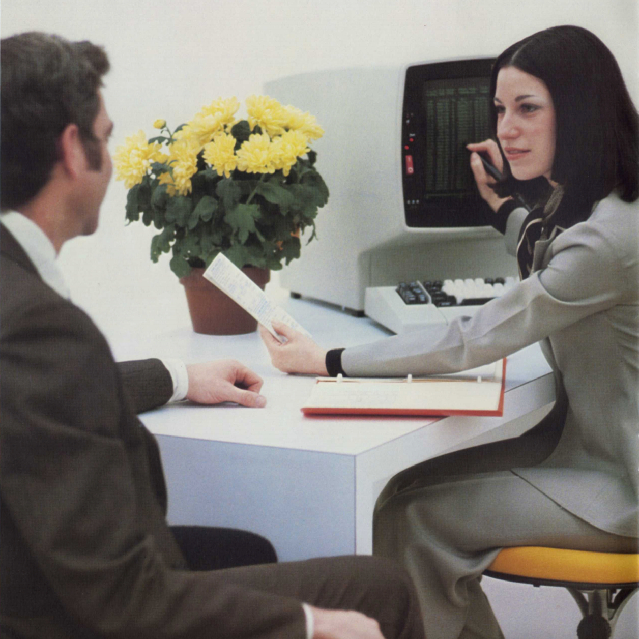 Photo of an IBM 3270 CRT, about as tall as the two people sitting in front of it
