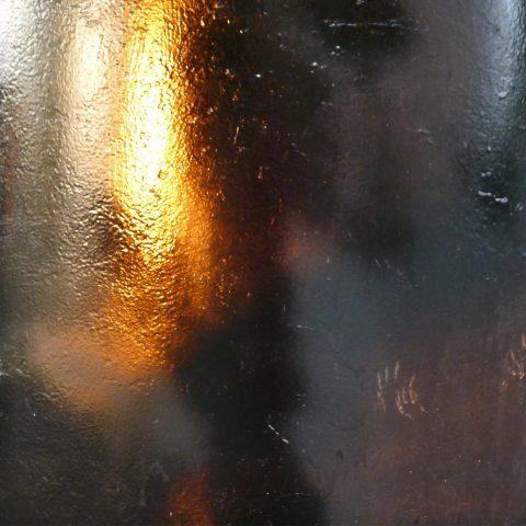 Abstract white orange glow on dark brown metal
