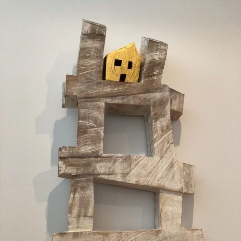 Wood sculpture of a gold house on a crooked ladder