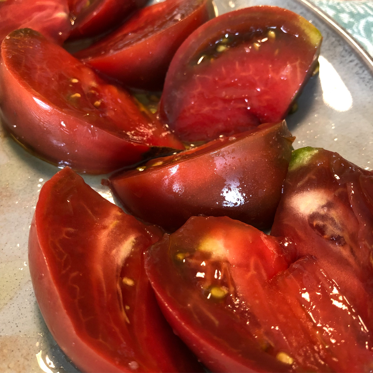 Sliced heirloom tomatoes, glistening with olive oil